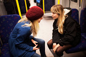 Two teenage girls talking on subway train