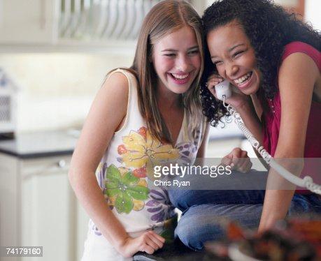Due ragazze adolescenti parlando al telefono Ridere
