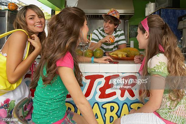 Two teenage girls talking with a bartender with another teenage girl standing beside them in a juice bar