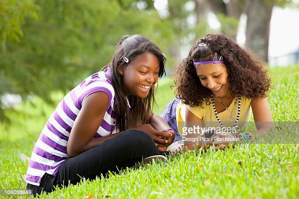 Two Teenage Girls Using Their Cell Phones While Laying On The Grass