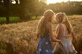 Two teenage girls walking in a barley field