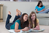 Two teenage girls watching television with her friend listening to an MP3 player