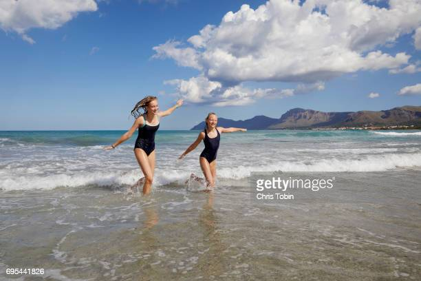 Two teenage girls with arms outstretched running through waves at beach