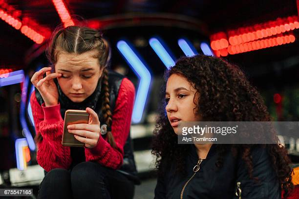 Two teenage girls with mobile phone at fairground