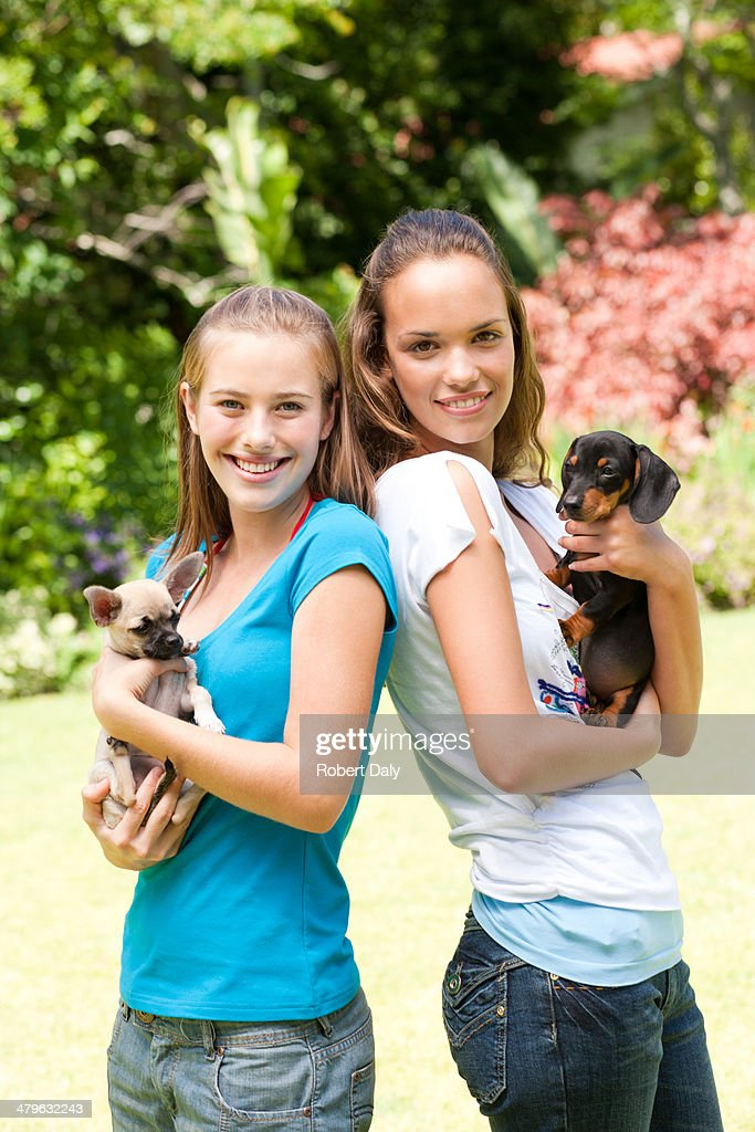 Two teenage girls with puppy dogs : Stock Photo