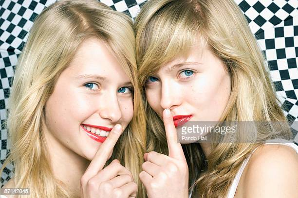 Two Teenage girls with red lips and finger on lips