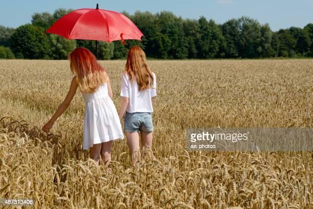 Zwei Teenager-Mädchen mit roten Sonnenschirm stehende Feld mit Gerste