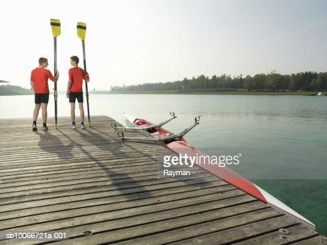 Two teenage rowers (16-17) holding oars, standing on pier looking at each other