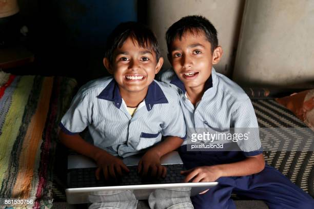Two teenager children's using laptop at home