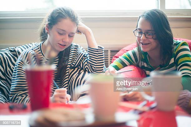 Two teenager girls play noughts and crosses