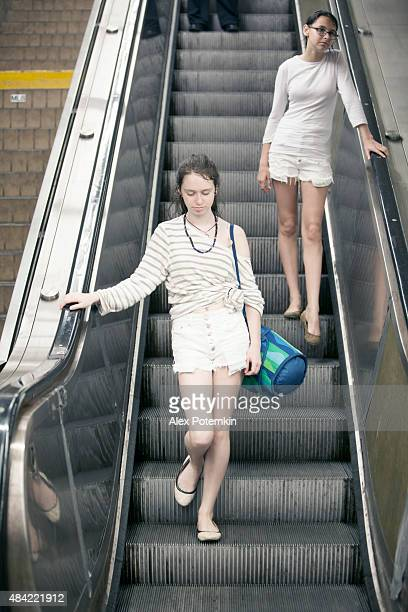 Two teenager girls riding an escalator down to subway station