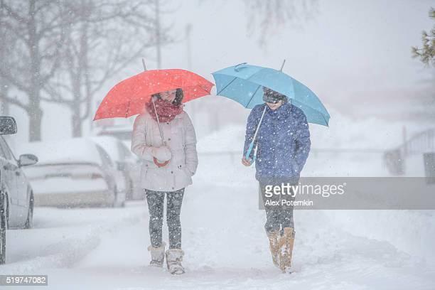 Duas meninas adolescente com guarda-chuvas em snowfall na rua