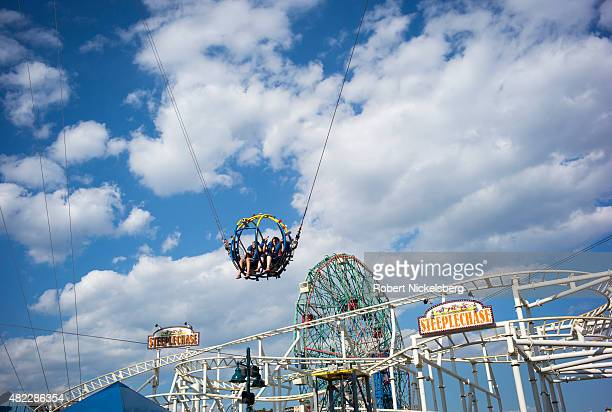 Two teenagers gaze out while strapped into the Sling Shot amusement park ride July 24 2015 at Coney Island Beach in the Brooklyn borough of New York