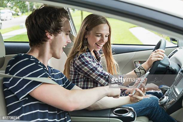 Two teenagers in a car, girl driving