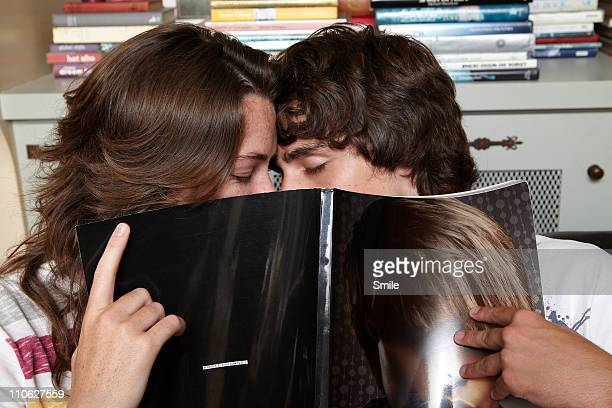 Two teenagers kissing behind magazine
