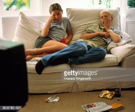 Two teenagers (12-14) relaxing on sofa, watching television : Stock Photo