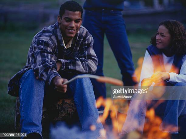 Two teenagers (16-17) roasting hot dogs over campfire in country field