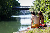 Two teenagers sit on the edge of the canal Charente in Angouleme on July 19 2016 to cool down as temperature might reach 40° by midday / AFP / Yohan...