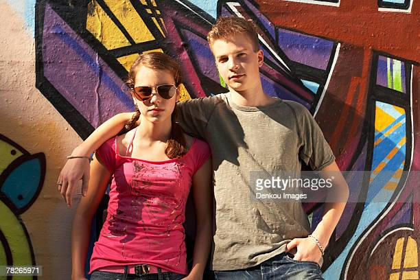 Two teenagers standing against a mural.