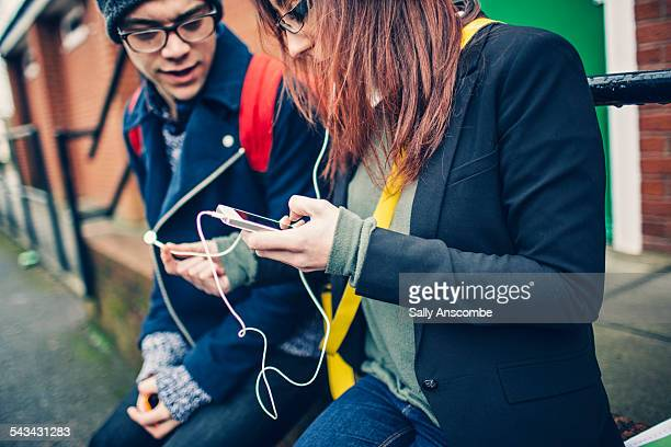 Two teenagers using a smart phone