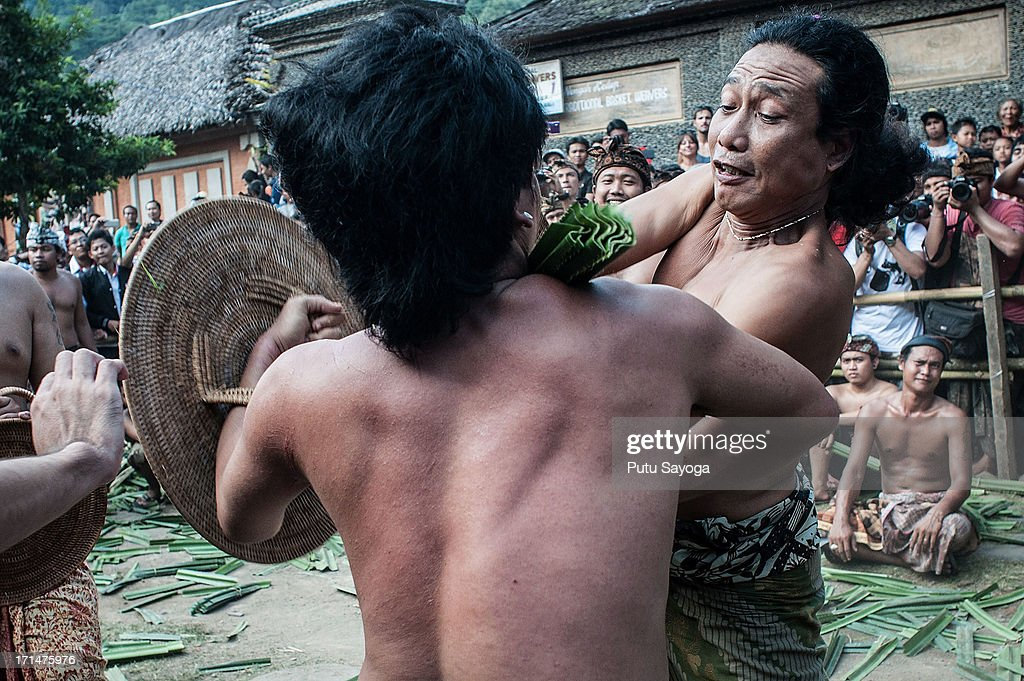 Two Tengananese men fight each other using thorny pandanus leaves on June 25, 2013 in Tenganan, Karangasem, Bali, Indonesia. Every year Tengananese people in the island of Bali celebrate a month-full ceremony called 'Usabha Sambah', to demonstrate respect to the God Indra, the Hindu god of war. One of the rituals during the ceremony is a Pandanus War or 'Mekare Kare', where two Tengananese men duel using thorny pandanus as their weapon.
