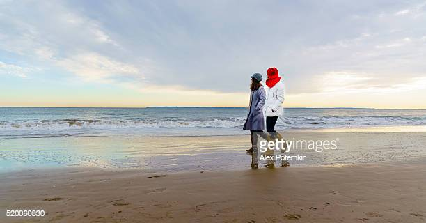 Two tennager girls walking at the beach