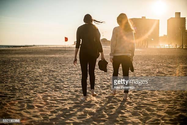 Two tennager girls walking at the Coney Island beach, Brooklyn
