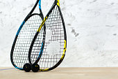 Close up of two tennis rackets and black balls over white wall background - sport, fitness, healthy lifestyle and objects concept