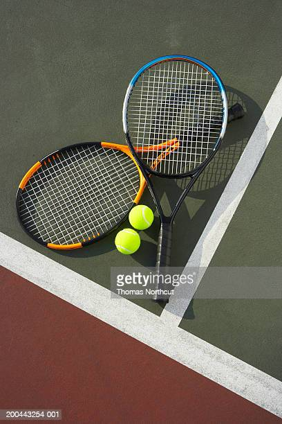 Two tennis rackets and tennis balls on tennis court, overhead view