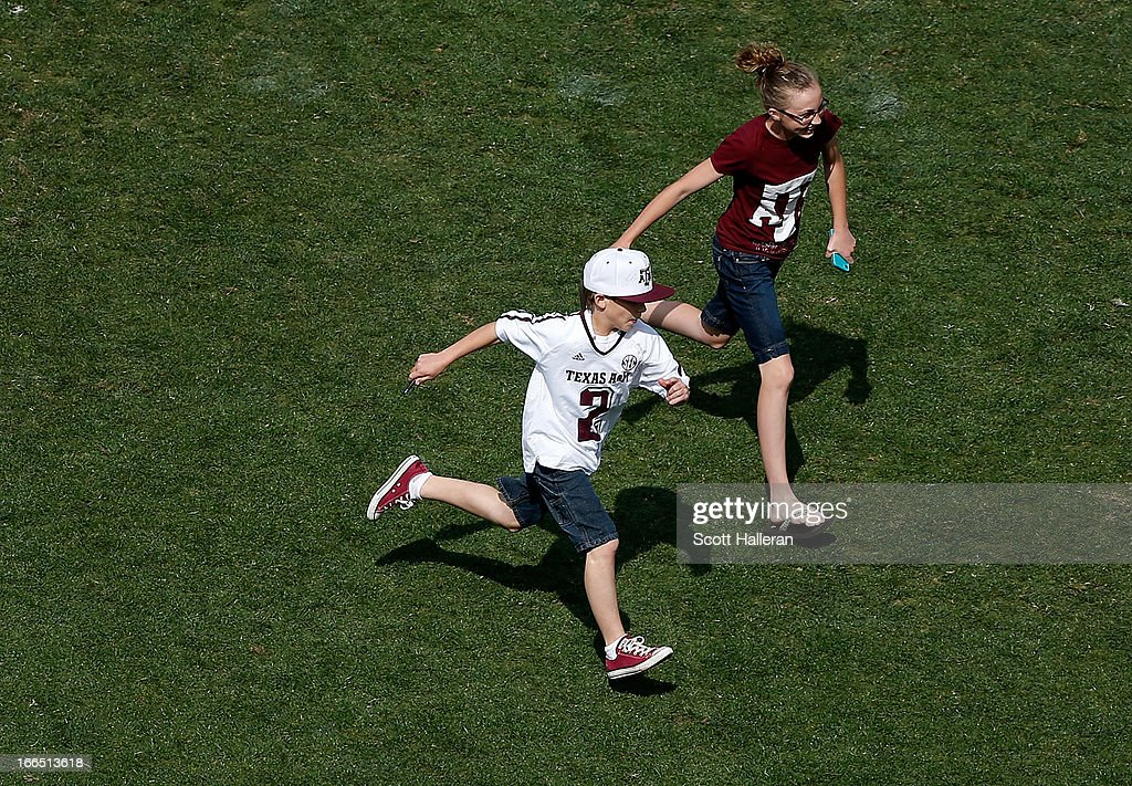 Two Texas A&M Aggies run off the field after quarterback Johnny Manziel signed an autograph them after the Maroon & White spring football game at Kyle Field on April 13, 2013 in College Station, Texas.