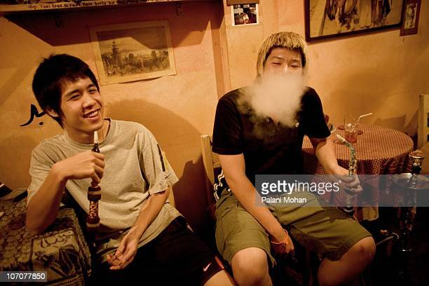 Two Thai teenagers smoke a shisha pipe at the hip 'To Sit' bar on Phra Athit Road in Bangkok on January 5 2007 in Bangkok Thailand The bar is one of...