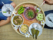 Two Thai women sit on a reed mat traditionally eating a selection of freshly cooked Northern Thai food. The food is on a traditional raised tray called 'Kantok'. In Northern Thailand it is traditional