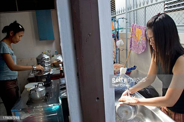 Two Thai women washing and cooking in a small kitchen area RELEASED