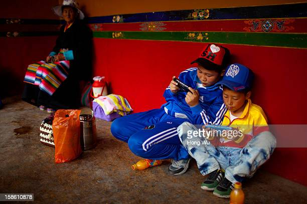 Two Tibetan children play games with their PlayStation Portable beside an elder Tibetan woman during the Sho Dun Festival in Norbulingka on August 18...