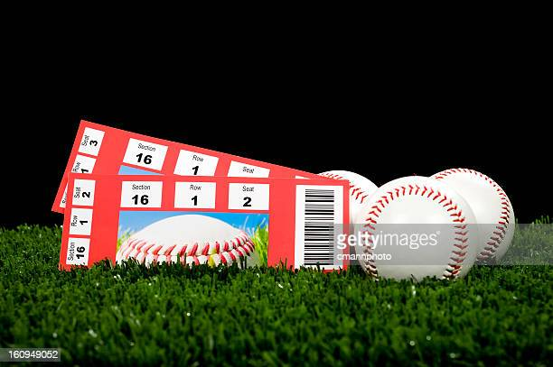 Two tickets of baseball games resting on grass with balls