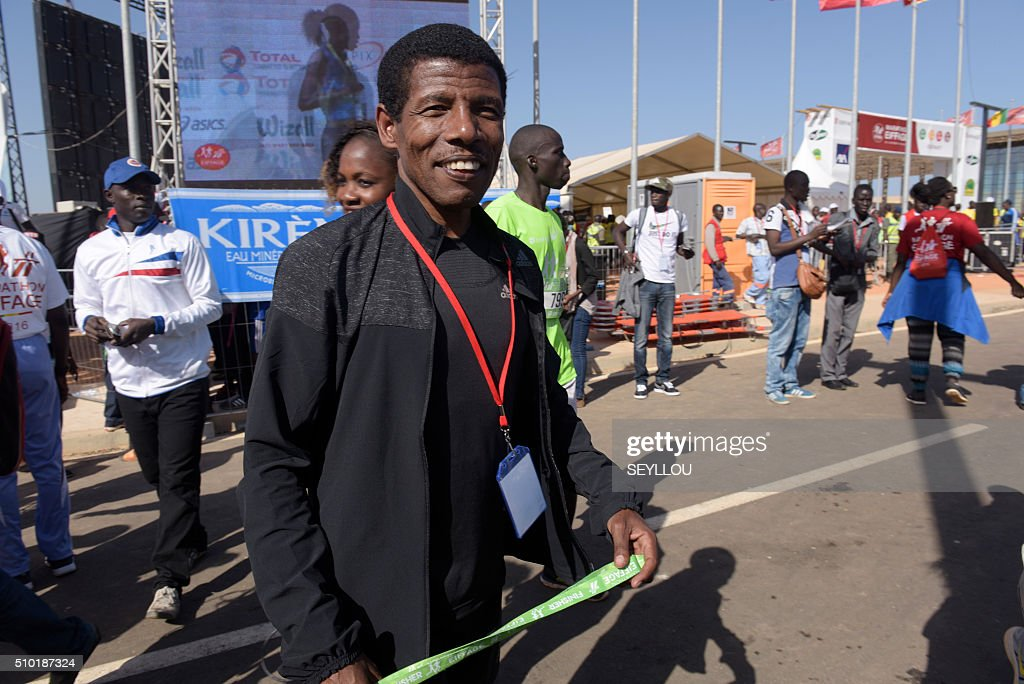 Two time Olympic gold winner and four time gold winner in the World Championships, retired Ethiopian long-distance track and road running athlete Haile Gebrselassie is seen at the finish line of the first ever Dakar International Marathon, in Dakar on February 14, 2016. The competition organised by the BTP Eiffage society started on February 13 in front of International Conference Center Abou Diouf (Cicad) on the outskirts of Dakar with different runs of 10 km culminariong with a marathon on February 14. The BTP Eiffage society hosted the event to celebrates its 90 years of presence in Senegal. / AFP / SEYLLOU