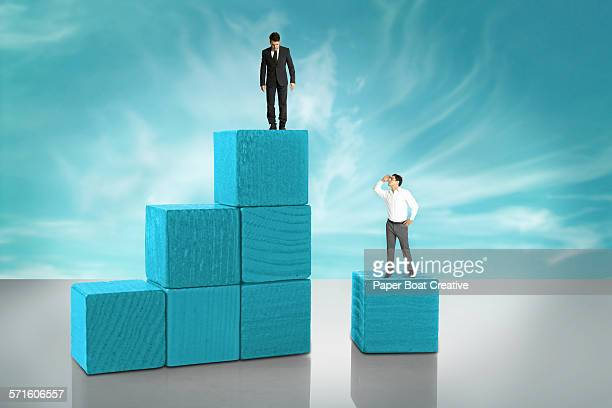 Two tiny businessmen on wooden blocks