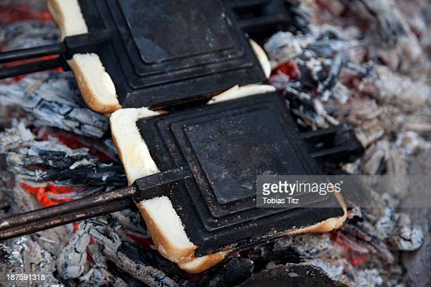 Two toasted sandwich makers on the campfire