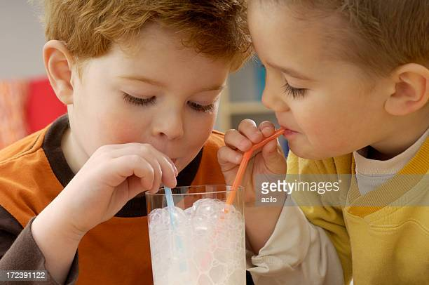 Two toddlers drinking milk in a glass with two straws