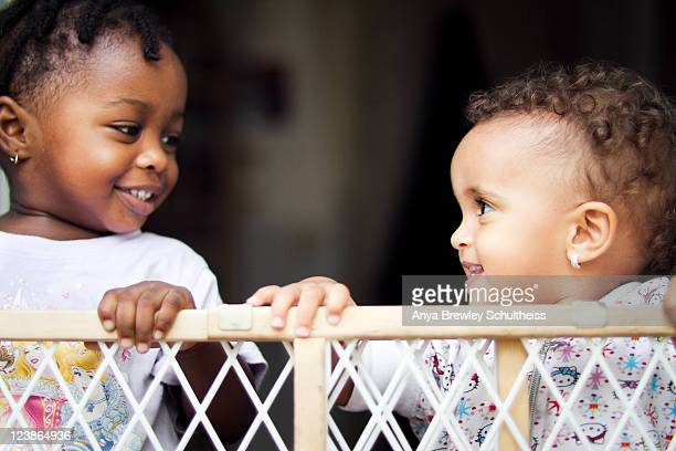 Two toddlers looking at each other and smiling