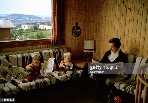 Two toddlers reading the newspaper with father