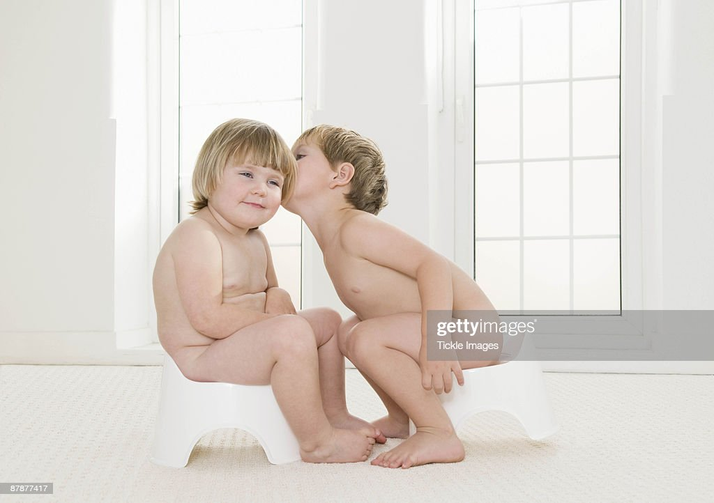 Two toddlers sitting on potties. : Stock Photo