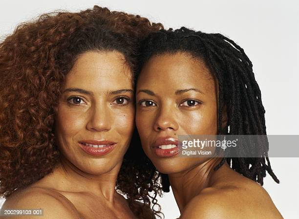 Two topless women, heads touching, portrait, close-up
