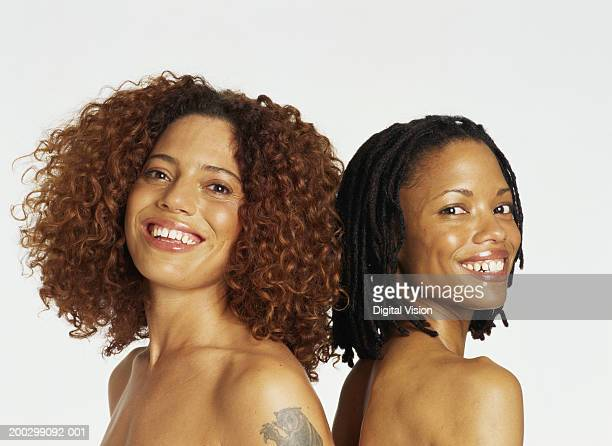 Two topless women standing back to back, smiling, portrait