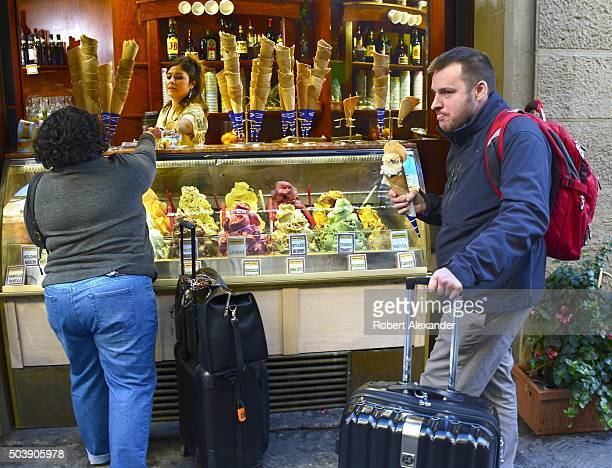 Two tourists buy and enjoy cones of gelato Italian ice cream in Florence Italy
