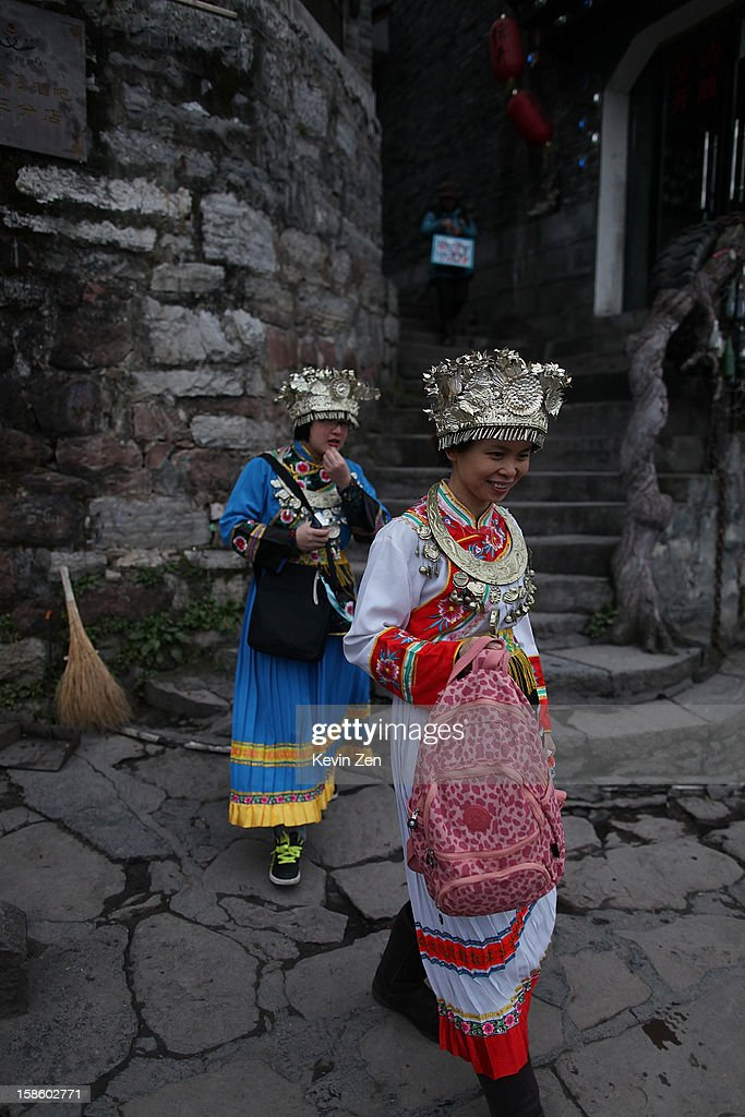 Two tourists dress Miao clothes, preparing for photo on December 18, 2012 in Fenghuang, China. Fenghuang Town was built by Emperor Kangxi in 1704 and after 300 years, the city's ancient appearance has been well preserved. Hunan is located in southwest Hunan Provience of China with a population of 370,000 within a total area of 1700 square kilometers.