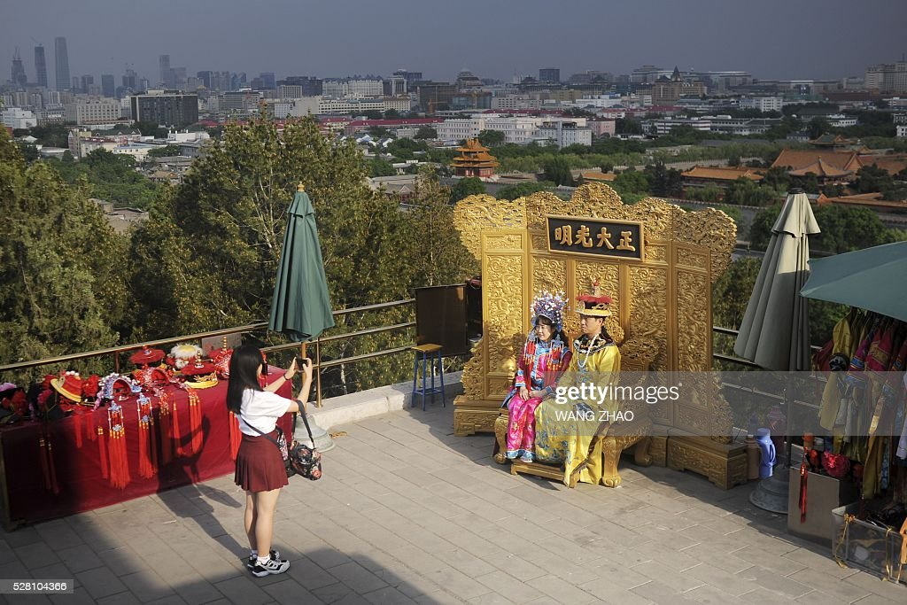 Two tourists dressed in Qing Dynasty clothing pose for a picture at a park near the Forbidden City in Beijing on May 4, 2016. / AFP / WANG
