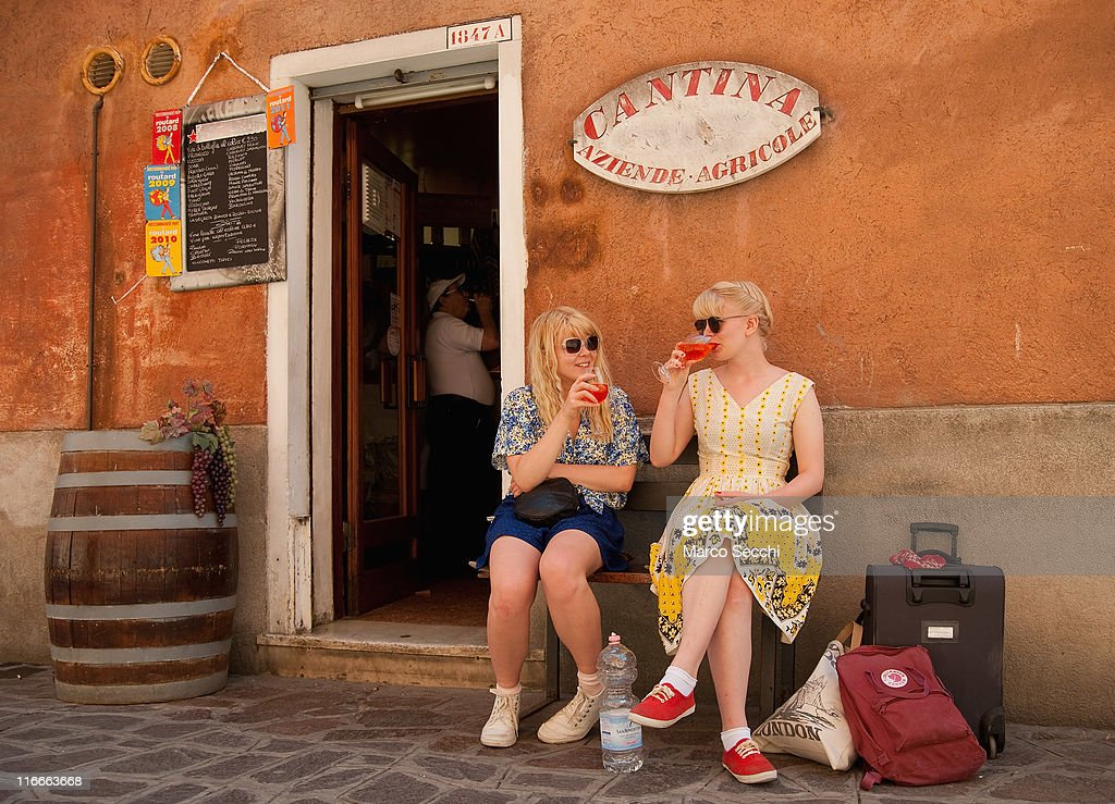 Two tourists enjoy a Spritz in front of a traditiona bacaro on June 17 2011 in Venice Italy The bacari are the local down to earth version of wine...