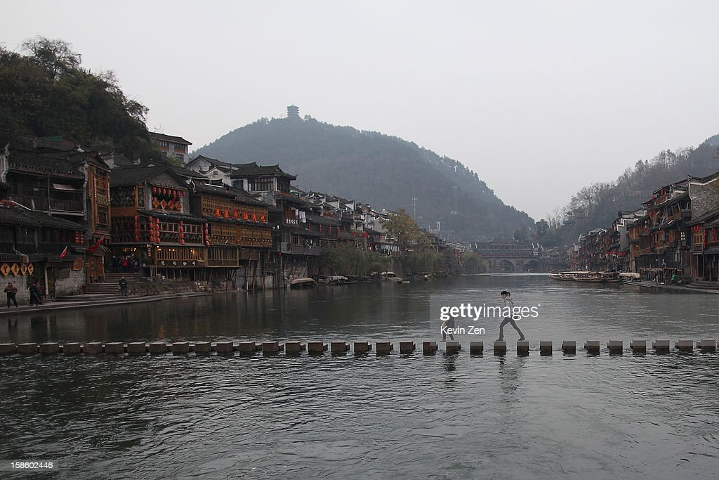 Two tourists go through a stone bridge on Tuojiang River on December 18, 2012 in Fenghuang, China. Fenghuang Town was built by Emperor Kangxi in 1704 and after 300 years, the city's ancient appearance has been well preserved. Hunan is located in southwest Hunan Provience of China with a population of 370,000 within a total area of 1700 square kilometers.