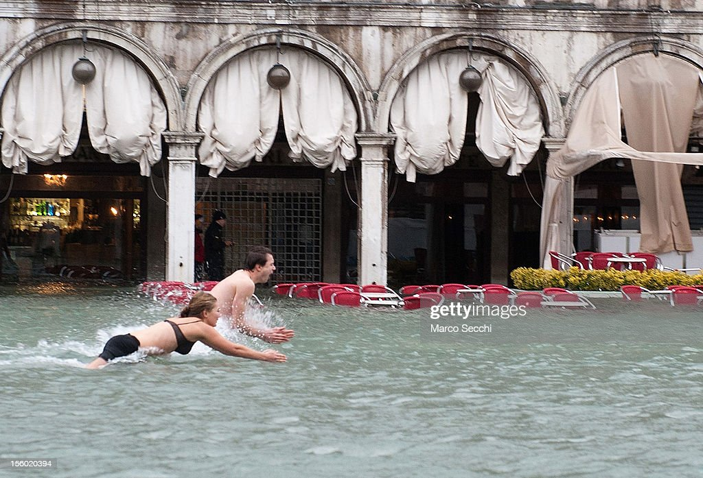 Two tourists jump into the water in Saint Mark's Square during the exceptional High Water on November 11, 2012 in Venice, Italy. More than 70% of Venice has been been left flooded, after the historic town was hit by exceptionally and unexpected high tide. The sea level rose very quickly to 150 due as well to strong southerly wind and heavy rain.